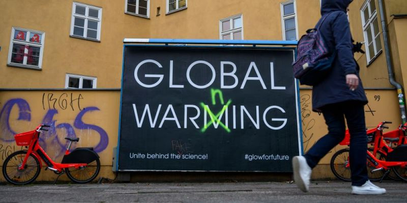 Billboard in Berlin warns people to acknowledge all the challenges posed by global warming. Photo by JOHN MACDOUGALL/AFP via Getty Images.