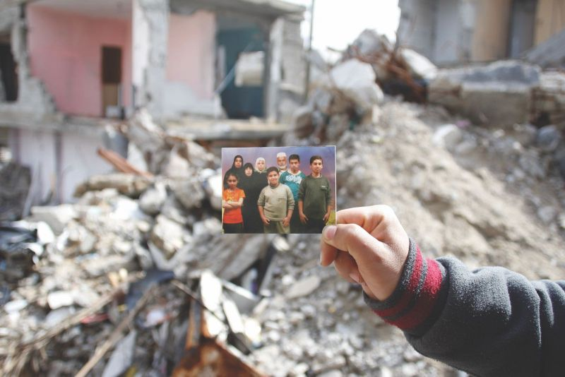 Jehad al-Saftawi Yassir Mahmoud El Haj holding a picture of his family, who, except for his sister, were all killed in a 2014 Israeli bombardment of their house in Khan Younis, Gaza, February 22, 2015