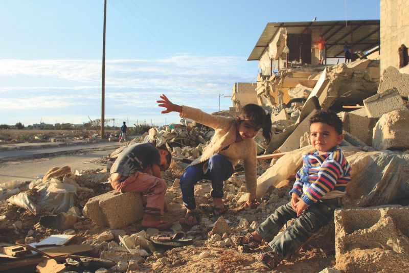 Jehad al-Saftawi Children sitting outside the bombed-out ruins of their home in Khuza'a, Gaza, September 30, 2014
