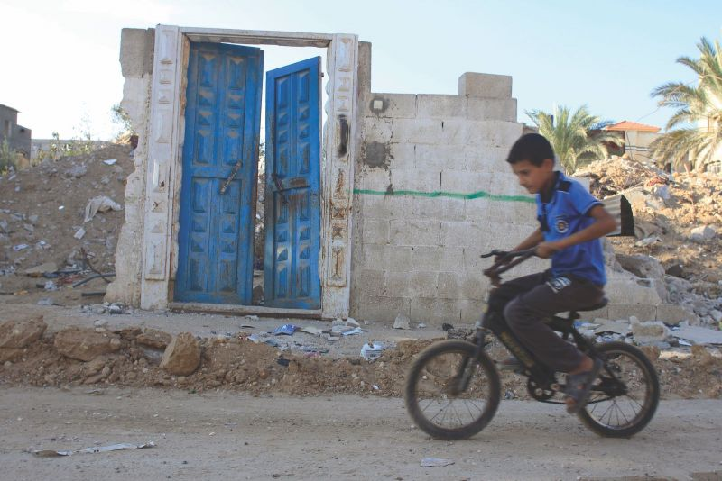 Jehad al-Saftawi A child biking past a door in Khuza'a, where hundreds of homes were destroyed in Israel's Operation Protective Edge, Gaza, October 14, 2014