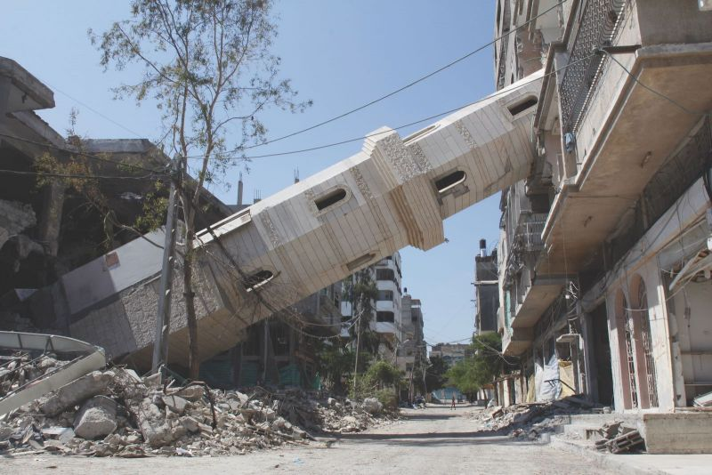 Jehad al-Saftawi The minaret of the al-Soussi Masjid leaning into an apartment building in the Beach refugee camp, after the mosque was targeted by Israeli drone strikes, Gaza, August 22, 2014