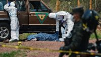 Officers of the Criminal Investigation Unit wearing protective suits to avoid possible contagion with the novel coronavirus, COVID-19, cover the corpse of a member of the Rapid Response Patrol who was shot dead in Tegucigalpa on 18 May 2020. Orlando SIERRA / AFP