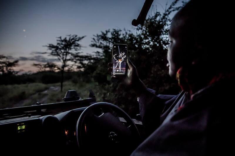 Safari guide Jimmy Lemara Sengeny uses a stargazing app when leaving Porini Camps early on June 19 in Kenya's Ol Kinyei Conservancy. (Luis Tato for The Washington Post)