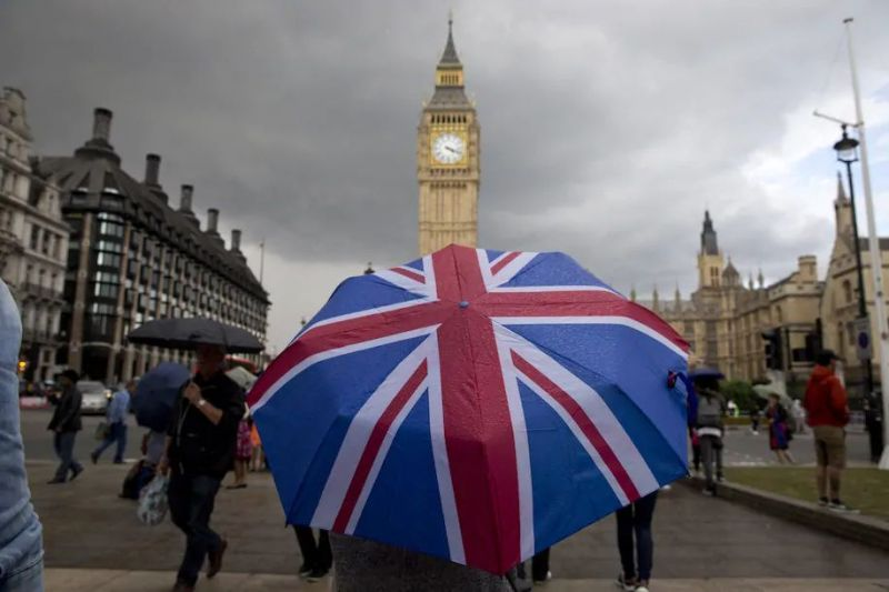 A pedestrian carries a Union-flag themed umbrella near Big Ben and Parliament in central London in 2016 shortly after the Brexit vote. (Justin Tallis/AFP via Getty Images)