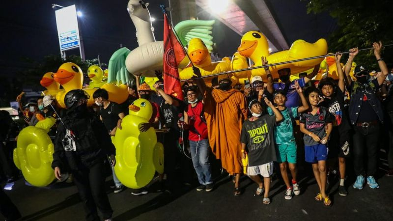 A Buddhist monk walks with pro-democracy protesters as they carry large inflatable ducks during a march to the 11th Infantry Regiment as part of an anti-government rally in Bangkok on 29 November 2020. Jack TAYLOR / AFP