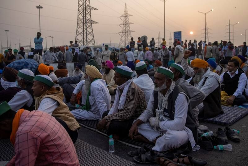 Farmers listen to a speaker on a blocked highway during their protest against recently passed farm bills, at the Delhi-Uttar Pradesh border in Ghaziabad, India, on Monday. (Danish Siddiqui/Reuters)