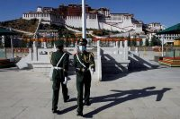 Paramilitary police officers swap positions during a change of guard in front of the Potala Palace in Lhasa, Tibert, in October. (Thomas Peter/Reuters)