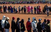 People affected by the pandemic-related downturn line up in May to receive food donations near Laudium, South Africa. (Themba Hadebe/AP)