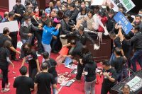 Lawmakers fight during a parliamentary session in Taipei, Taiwan, on Nov. 27, by throwing punches and pig guts at each other over a policy that would allow imports of U.S. pork and beef. (FTV/AP)