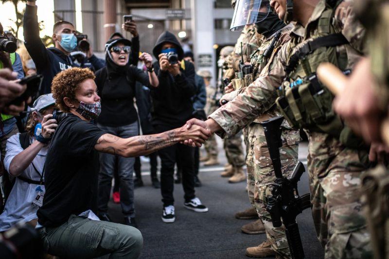 Un manifestante estrecha la mano de un miembro de la Guardia Nacional de Estados Unidos en Los Ángeles el 31 de mayo de 2020. Credit Bryan Denton para The New York Times