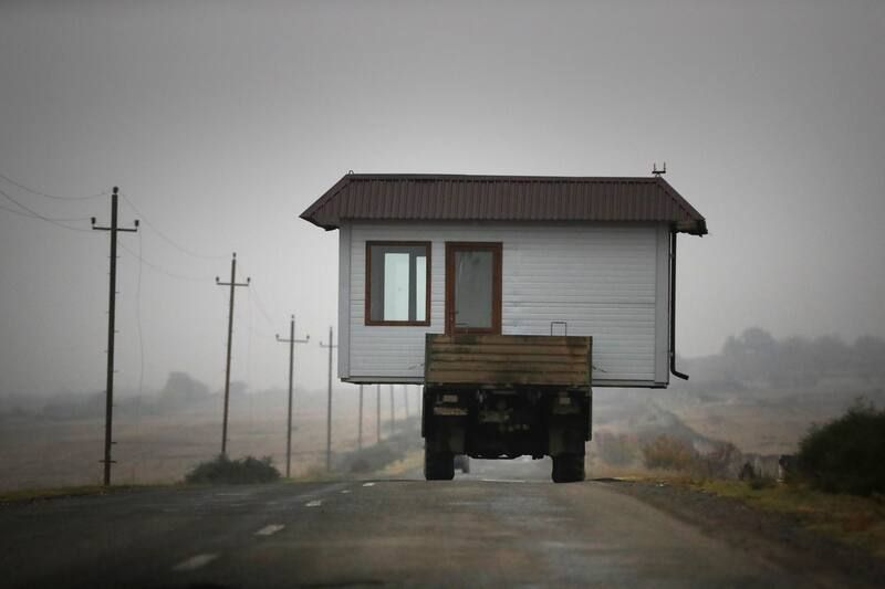 A family drives a truck loaded with a small house along a highway as they leave their home village in the disputed region of Nagorno-Karabakh on Nov. 18, before a cease-fire takes effect to halt weeks of fighting. (AP Photo/Sergei Grits)