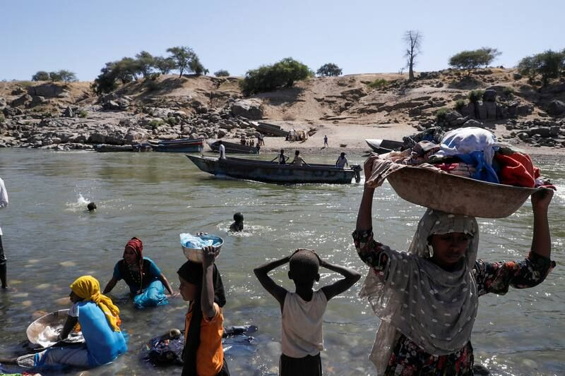 Refugees on Monday stand on the bank of a river that separates Sudan and Ethiopia. (Baz Ratner/Reuters)