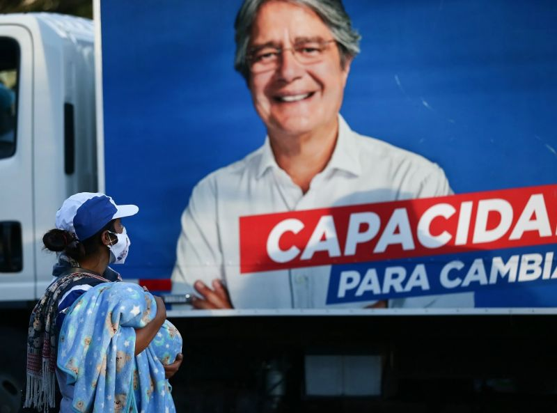 Una mujer ve una pancarta de la campaña de Guillermo Lasso en Quito, la capital de Ecuador, el 11 de enero de 2021. Credit Jose Jacome/EPA vía Shutterstock