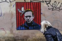 A woman looks at a large poster in Rome depicting Russian opposition leader Alexei Navalny behind bars with a dove freeing him from detention in Moscow. (Fabio Frustaci/EPA-EFE/REX/Shutterstock)