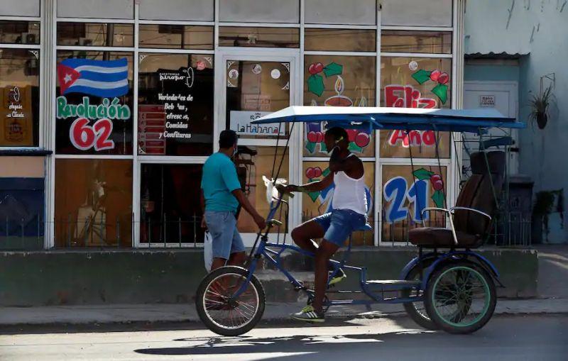 Dos personas pasan por una cafetería con imágenes anunciando los 62 años de la Revolución Cubana y deseando un feliz año nuevo, en La Habana, Cuba, el 16 de diciembre de 2020. (Ernesto Mastrascusa/EPA-EFE/Shutterstock)