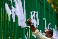 A man ties a white ribbon to a fence at a cemetery in Colombo, Sri Lanka, on Dec. 23 to protest the government policy of forced cremations of Muslims who die of covid-19. (Lakruwan Wanniarachchi/AFP/Getty Images)