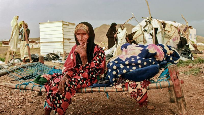 An elderly woman looks on while sitting on a make-shift bed as people try to salvage tents damaged by torrential rain, at a camp for Yemenis displaced by conflict in the northern Hajjah province on 30 September 2020. Essa Ahmed/AFP