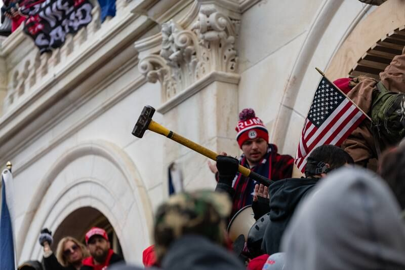 Rioters pass a sledgehammer forward in their attempt to enter the U.S. Capitol. (Eric Lee/Bloomberg News)