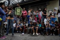 Un grupo de personas hacen fila para recibir donativos en una calle de Caracas, el 6 de enero de 2021. Credit Rayner Peña R/EPA vía Shutterstock