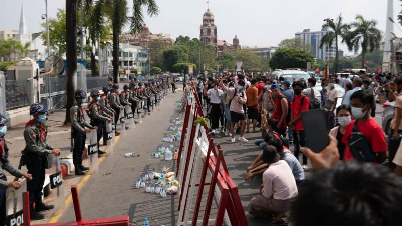 """Riot police face off against a crowd of demonstrators in front of Yangon's City Hall. The crowd is chanting """"the people's police"""" and has given them roses, water and snacks to signify that their protest is against the military junta. 7 February 2021. CRISISGROUP/Richard Horsey"""