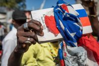 A copy of the Haitian Constitution wrapped in an American flag at a march in Port-au-Prince on Feb. 10. The Haitian president's supporters and opponents disagree on when his term ends. Credit Valerie Baeriswyl/Agence France-Presse — Getty Images