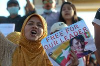 A demonstrator displays a placard calling for the release of detained Myanmar leader Aung San Suu Kyi during a protest on Feb. 10. (Str/AP)
