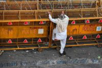 A farmer stands next to police barricades along a blocked highway as farmers continue to protest the central government's recent agricultural reforms on Feb. 2. (Prakash Singh/AFP/Getty Images)