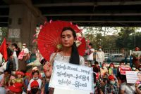 """An anti-coup protester holds a Burmese sign that reads """"Return our leader Mother Suu and our President Win Myint"""" outside the Hledan Centre in Yangon, Myanmar. (AP)"""