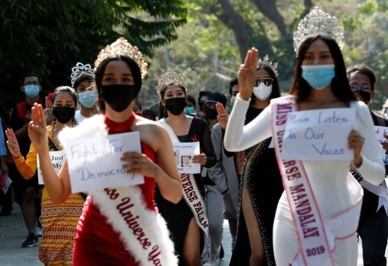 Participants of beauty pageants flash the three-finger salute and hold placards during a protest the military coup on Feb. 10 in Yangon, Myanmar. (Nyein Chan Naing/EPA-EFE/REX/Shutterstock)