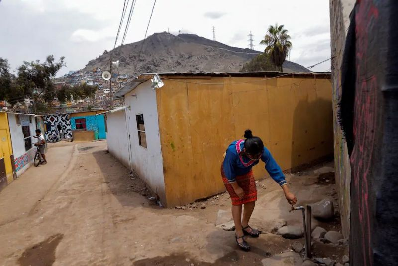 A woman of the Shipibo-Konibo ethnic group uses a water tap in a community along the Rímac River, in Lima, Peru, in February. (Luis Angel Gonzales/EPA-EFE/Shutterstock)