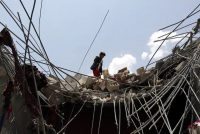 A Yemeni looks through the wreckage of a building after it was hit by an airstrike on the northern outskirts of the capital, Sanaa, in 2017. (Yahya Arhab/EPA)