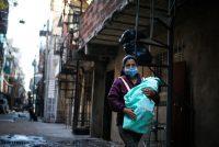 Una mujer, con un bebé en brazos, camina por una calle de Villa 31, en Buenos Aires. Credit Juan Ignacio Roncoroni/EPA vía Shutterstock