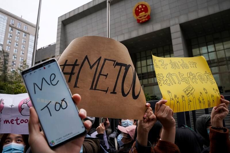 Supporters hold banners as they wait for Zhou Xiaoxuan outside the Beijing court hearing for her sexual harassment lawsuit on Dec. 2, 2020. (AP Photo/Andy Wong)