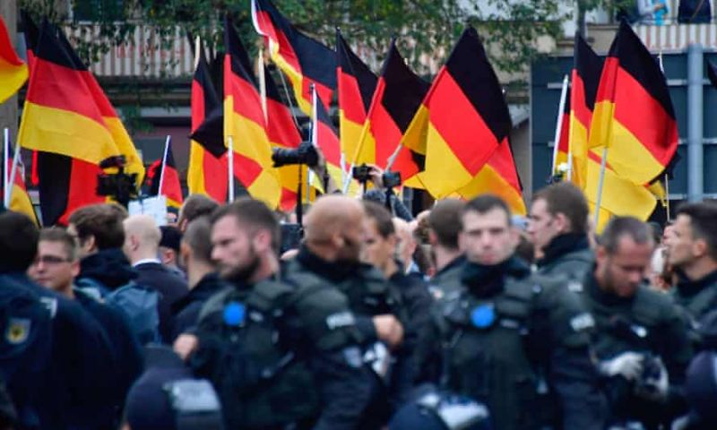 Supporters of the AfD party wave German flags as they walk behind police during a demonstration in Chemnitz, Germany, October 2020. Photograph: John MacDougall/AFP/Getty Images
