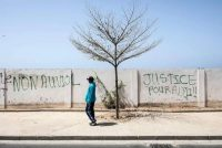 "A man walks past graffiti which says: ""Justice For Adji Sarr"" and ""No To Rape"" in Dakar on March 18, 2021. (John Wessels/AFP/Getty Images)"