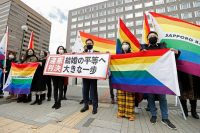 """Supporters hold rainbow flags and a banner that reads: """"Unconstitutional judgment"""" in Sapporo, Japan, on Wednesday. (Yohei Fukai/AP)"""