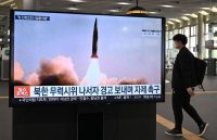 A man walks past a television screen at Suseo railway station in Seoul on March 26 showing news footage of North Korea's latest tactical guided missile test. (Jung Yeon-je/AFP/Getty Images)