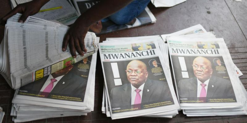 News headlines announce the death of Tanzanian president John Magufuli at the business center in Kariakoo, Dar Es Salaam. Photo by AFP via Getty Images.