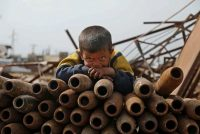 A Syrian child poses atop a stack of neutralized shells at a metal scrapyard in the northwestern Idlib province on Wednesday. (Aaref Watad/AFP/Getty Images)