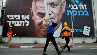Labourers walk past a Blue and White party election campaign banner depicting its leader, Israeli Defence Minister Benny Gantz, alongside Israeli Prime Minister Benjamin Netanyahu ahead of the March 23 ballot, in Tel Aviv, Israel March 14, 2021. REUTERS/Corinna Kern
