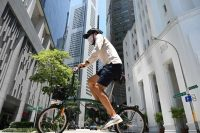 A man rides a bicycle along a street at the Raffles Place financial business district in Singapore on Tuesday. (Roslan Rahman/AFP/Getty Images)