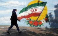 A woman walks next to a wall painting of Iran's national flag in Tehran on April 18. (Abedin Taherkenareh/EPA-EFE/Shutterstock)