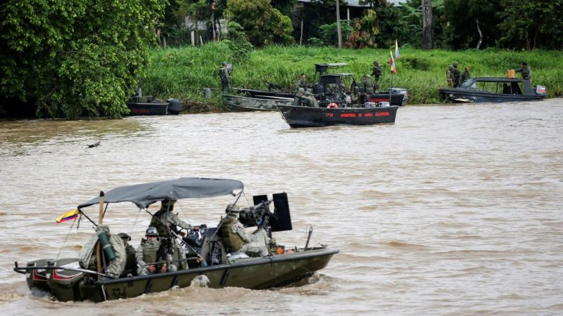 A Colombian navy boat patrols the Arauca river while a Venezuelan navy boat remains anchored on the border between Colombia and Venezuela, as seen from Arauquita, Colombia 28 March 2021. REUTERS/Luisa Gonzalez