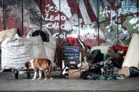 Un hombre en situación de calle descansa junto a sus perros y pertenencias, en Villa 21, en Buenos Aires, Argentina, el 29 de marzo de 2021. (Juan Ignacio Roncoroni/EPA-EFE/Shutterstock)
