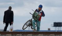 A Chinese worker on the Mombasa-Nairobi railway carries his bicycle, used for getting around the construction site, across train tracks near Syokimau station in Nairobi in 2016. (Ben Curtis/AP)