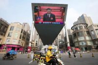 Chinese President Xi Jinping is seen on a big screen during a live broadcast of the closing session of the National People's Congress in Beijing on March 11. (Ng Han Guan/AP)