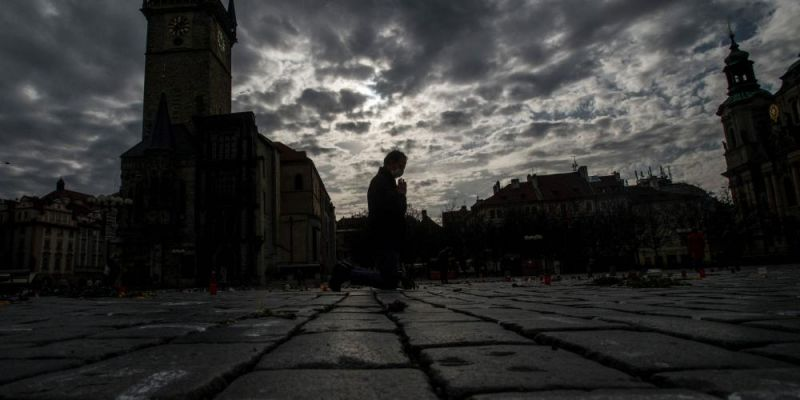A man prays in the Old Town Square in Prague, Czech Republic. Photo by MICHAL CIZEK/AFP via Getty Images.