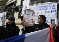 """Women hold signs reading """"Don't touch my headscarf"""" as they demonstrate Oct. 19, 2019, on the Place de la Republique in Paris. (DOMINIQUE FAGET/AFP via Getty Images)"""