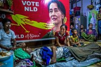 Relatives mourn a day laborer who was shot during an anti-coup protest on the outskirts of Yangon, Myanmar. A poster of Daw Aung San Suu Kyi, the nation's deposed de factor leader, hangs in the background. Credit Panos Pictures/Redux