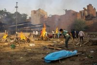 A man prepares a funeral pyre for a coronavirus victim at a cremation ground in New Delhi on Thursday. (Danish Siddiqui/Reuters)